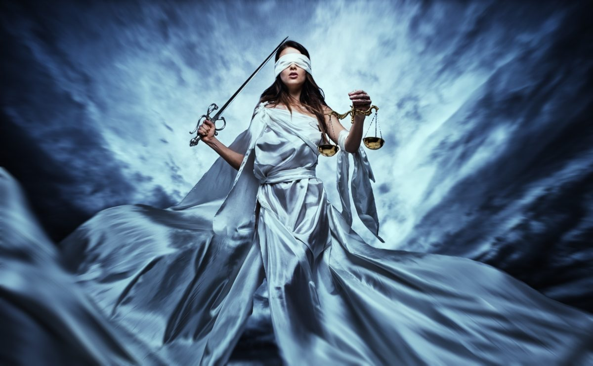 Femida, Goddess of Justice, with scales and sword wearing blindfold against dramatic stormy sky